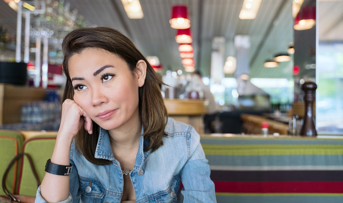 young asian woman looking annoyed and rolling her eyes at a diner