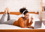 young black woman on bed singing on her computer with headphones