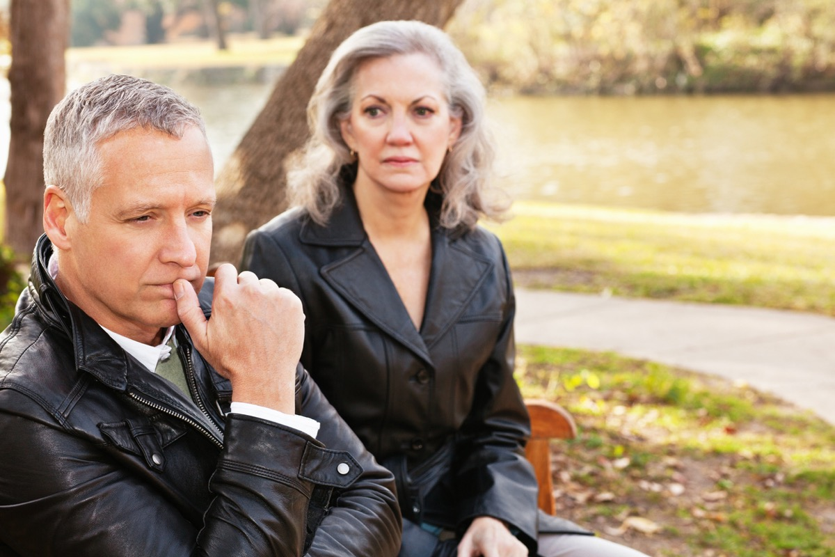 older white couple looking unhappy on a park bench