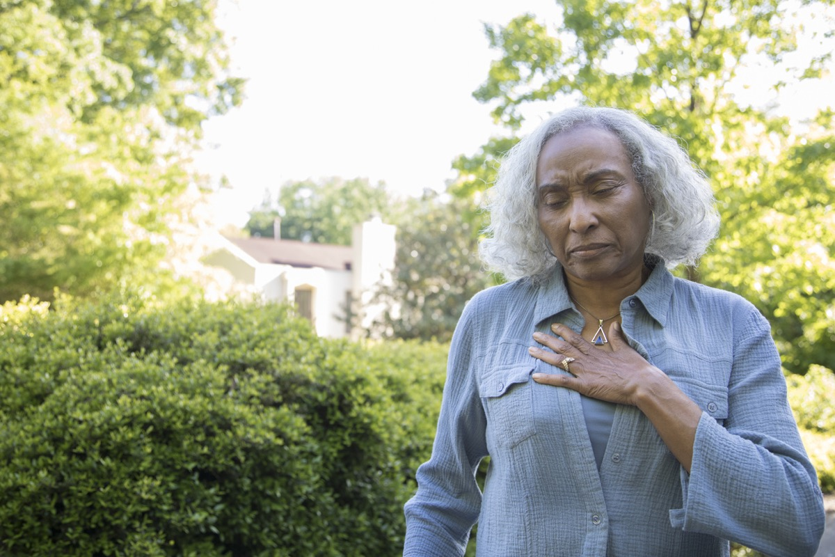 older black woman clutching her chest outside