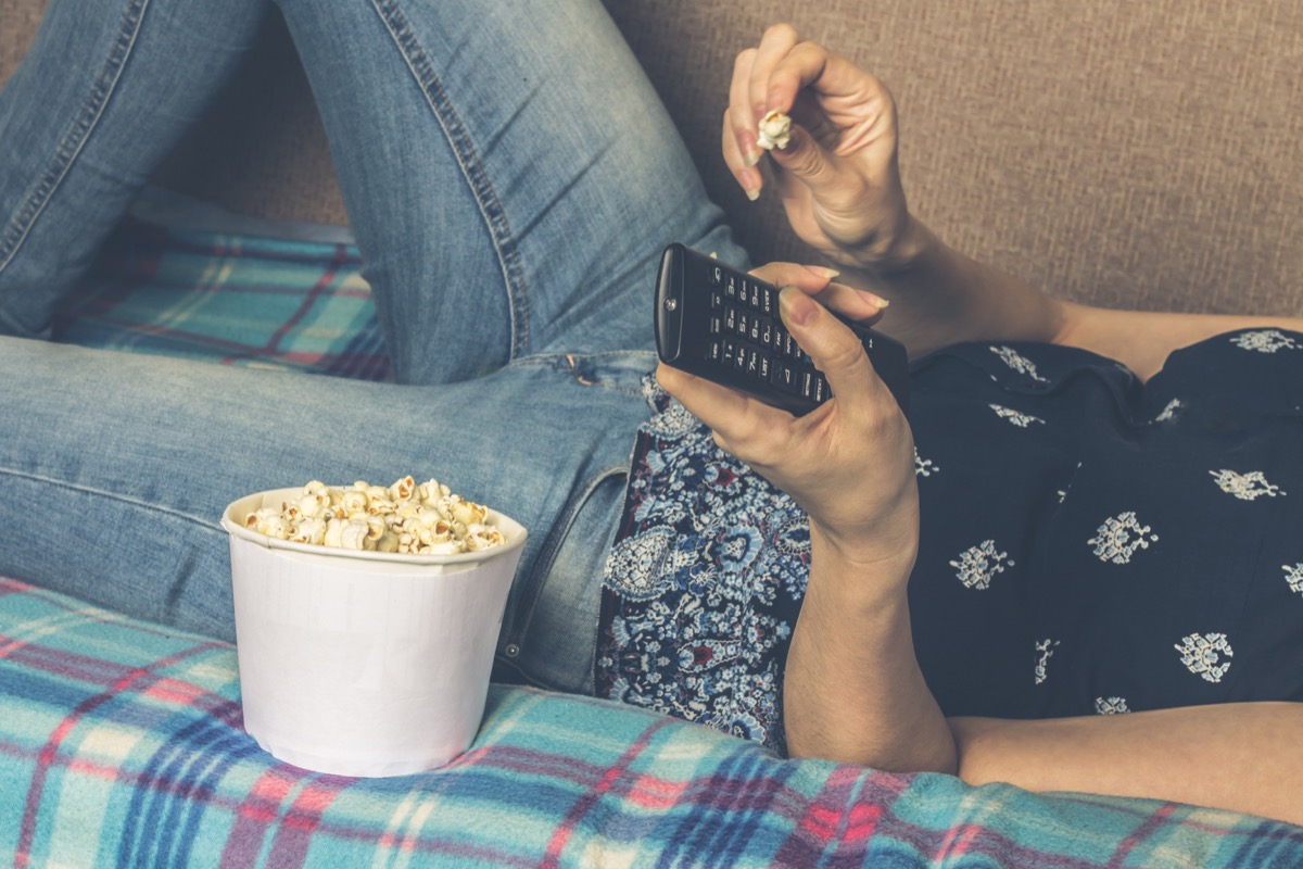 woman eating popcorn laying on the couch watching TV