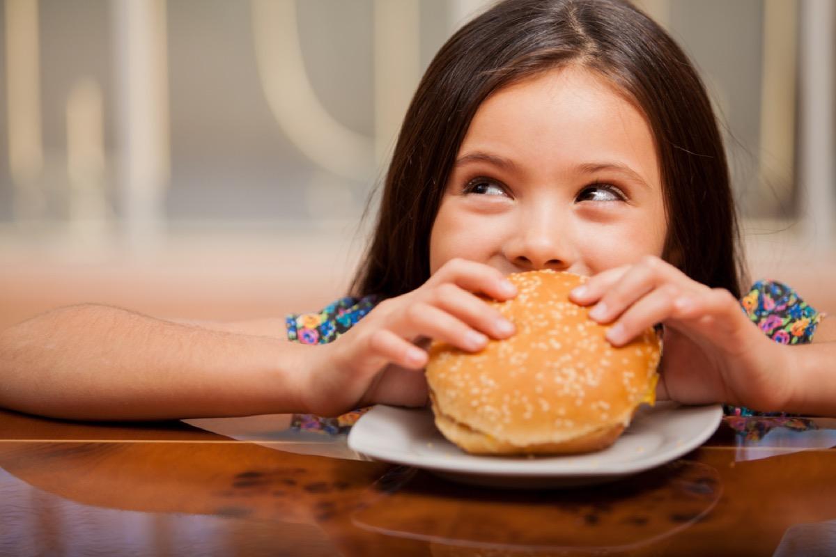 little girl eating hamburger, bad parenting