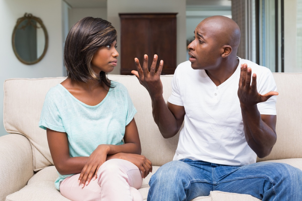 man fighting with girlfriend on couch, things you should never say to your spouse
