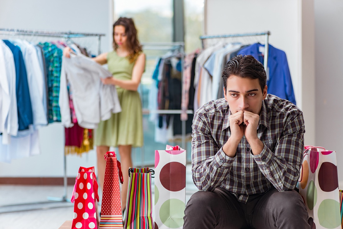 woman trying on clothes with bored spouse, things you should never say to your spouse