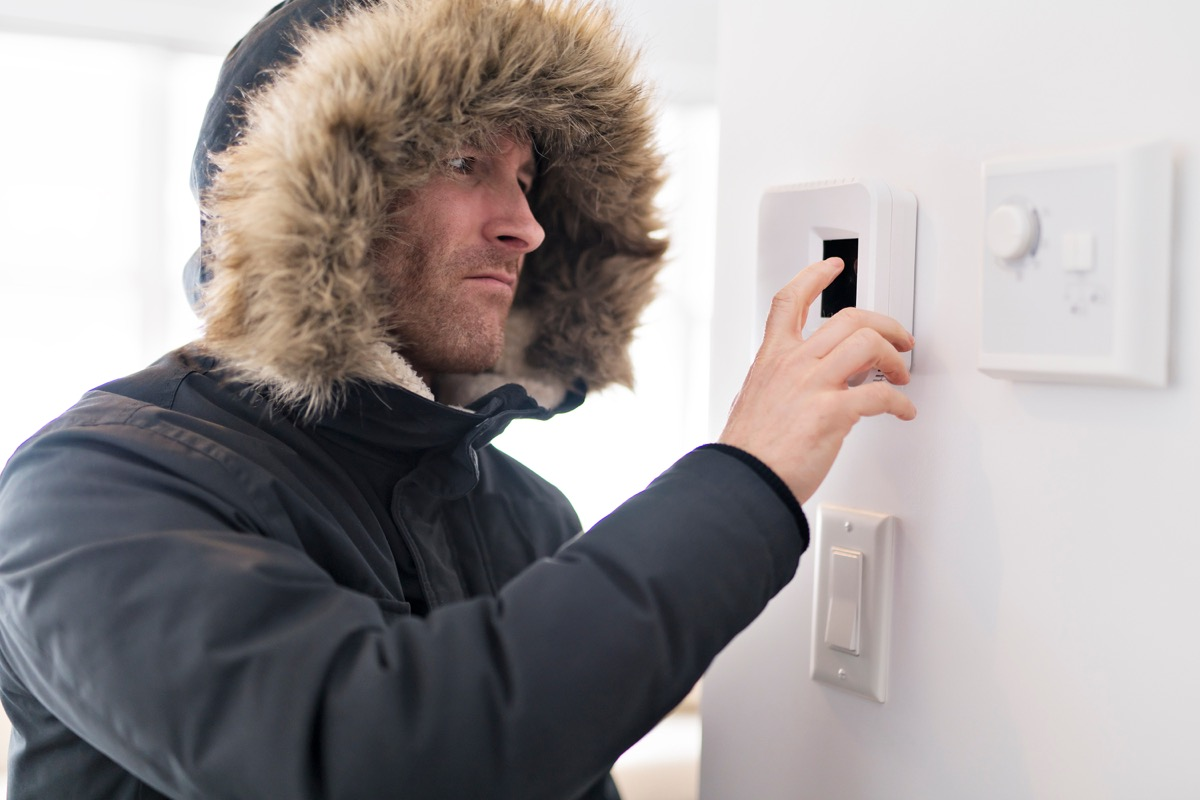 man whose cold wearing a jacket and turning up the temperature