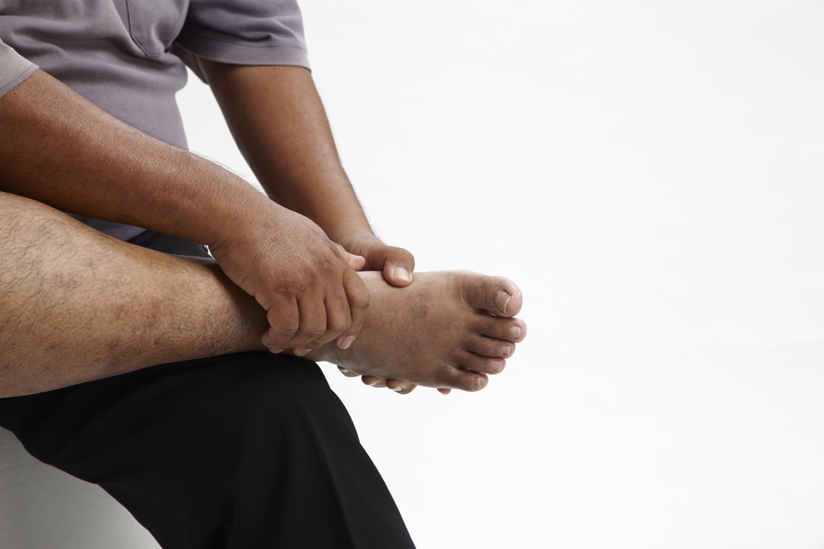 Man Holding His Foot in Pain Aching Feet