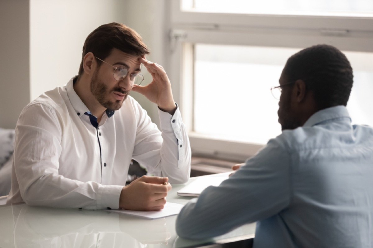 man holds head in hands while talking to another man