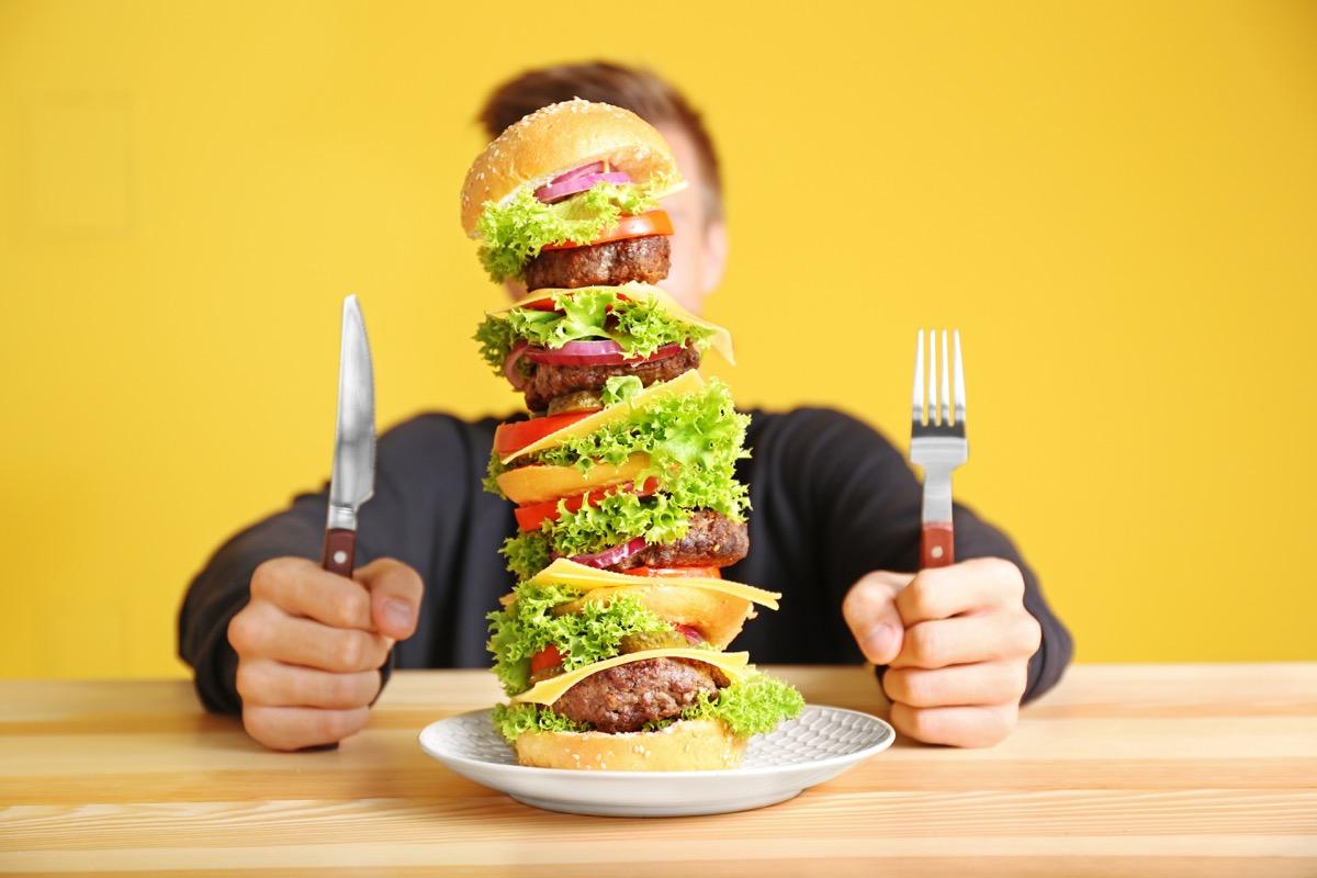 man eating huge burger