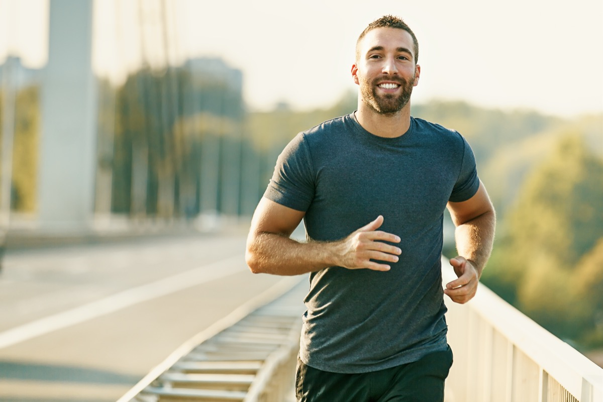 man running alone on the street smiling
