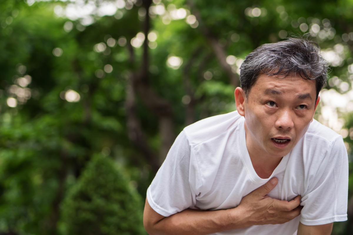 Man holding his chest having a hard time breathing