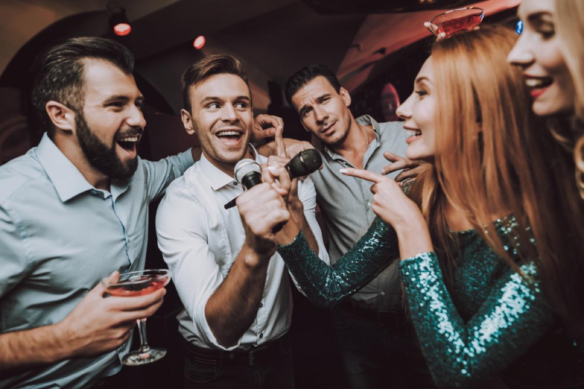 man singing karaoke while women watch, relationship white lies