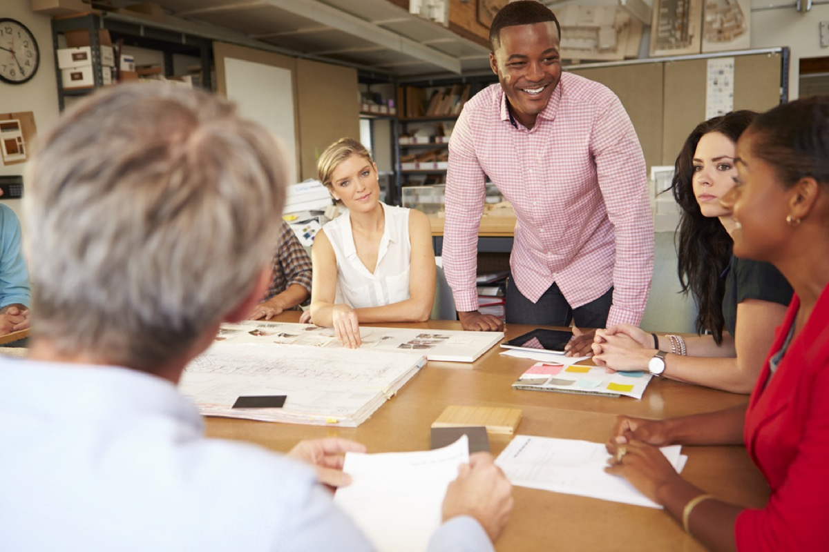 man standing up at desk with female employees seated, office etiquette