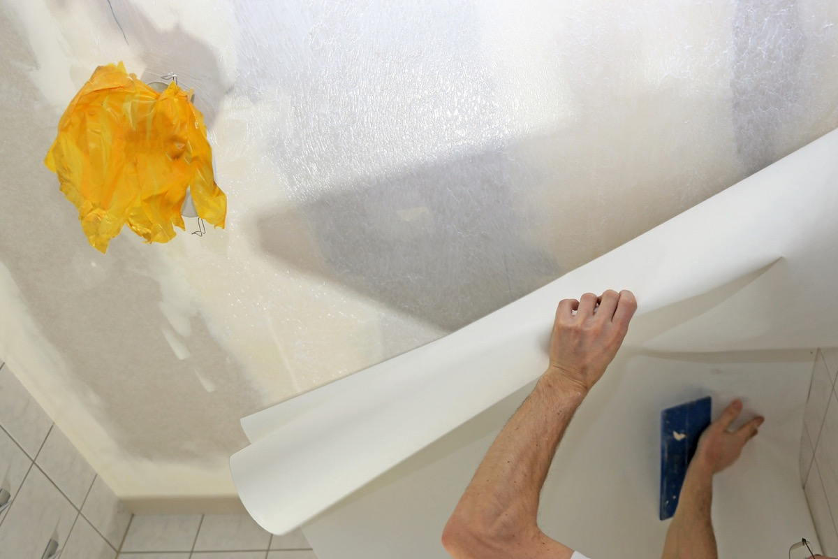 man wallpapering ceiling with white paper