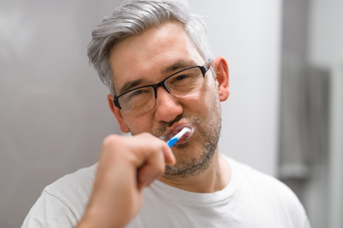 man with gray hair brushing teeth