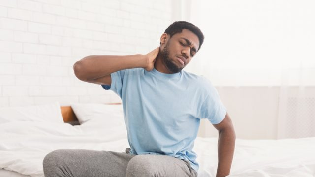 man with neck and back pain, signs your cold is serious