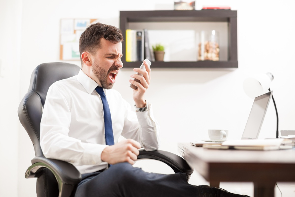 man shouting into phone signs of burnout