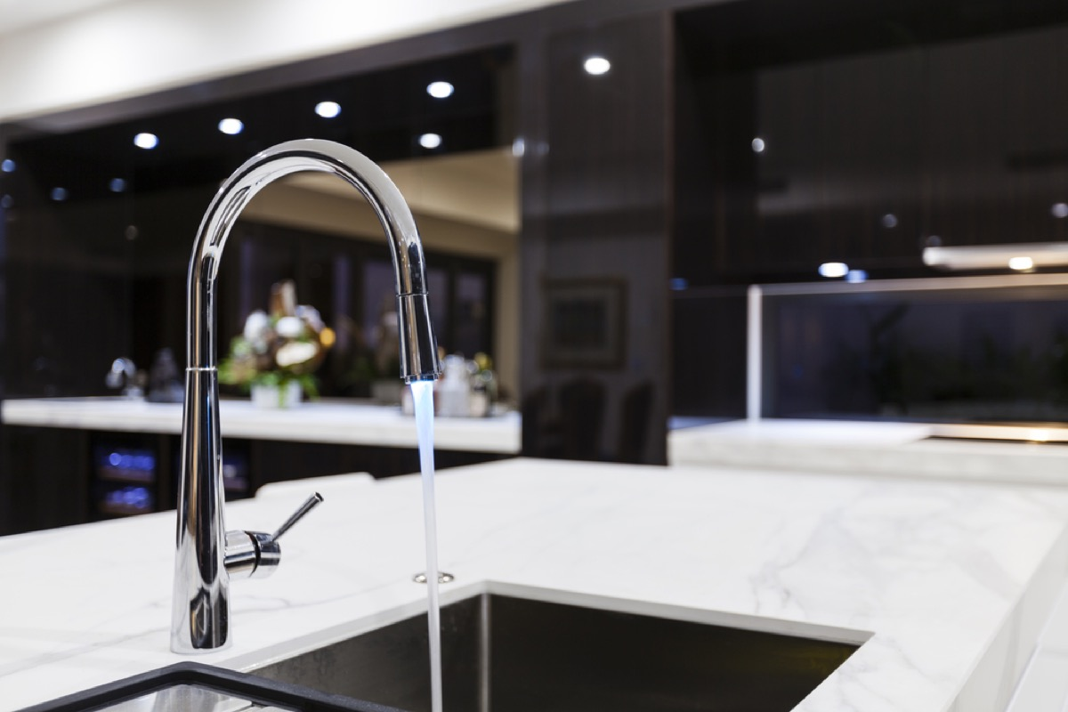 modern silver faucet with running water into sink