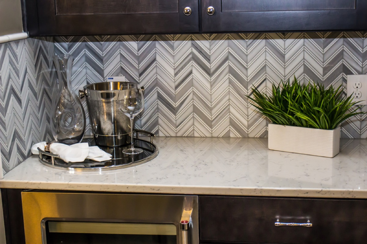 modern kitchen with dark cabinetry, white stone counters, and gray chevron backsplash