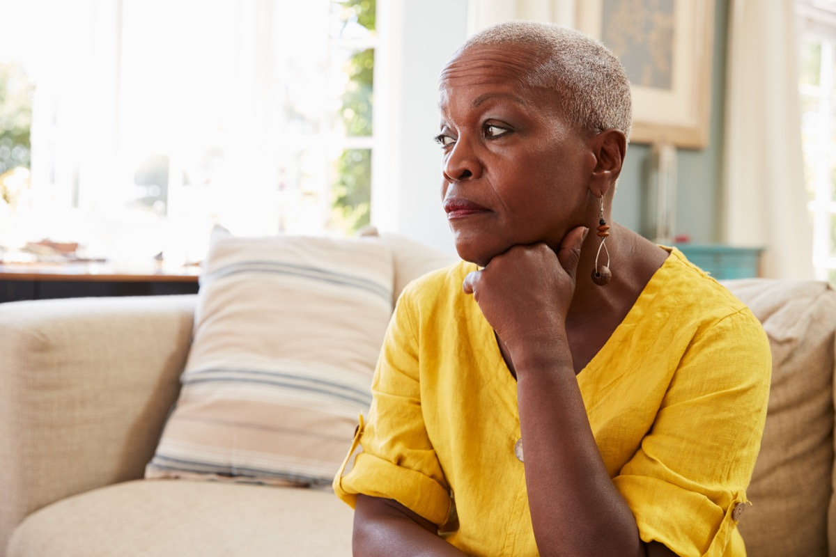 old worried woman sitting on the couch, single people