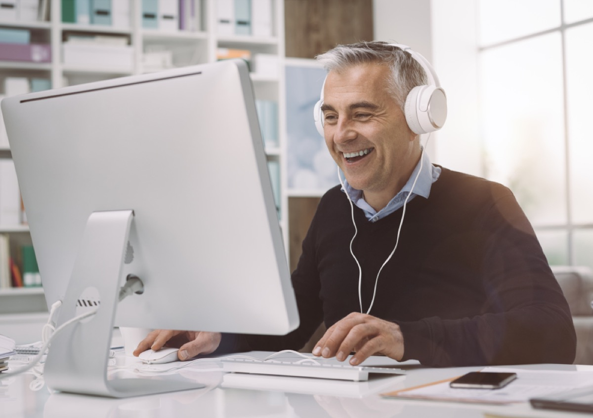 older man with gray hair wearing headphones at his desk, office etiquette