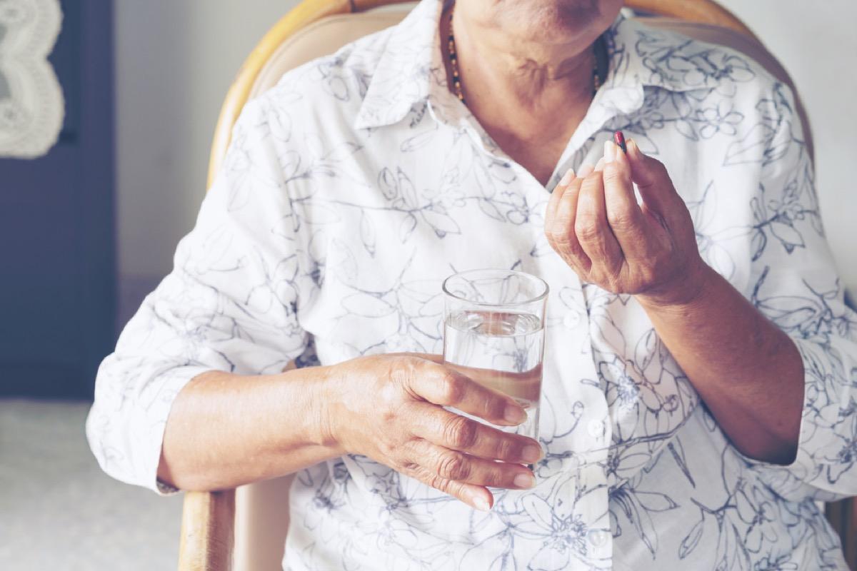 older woman taking medicine, heart risk factors