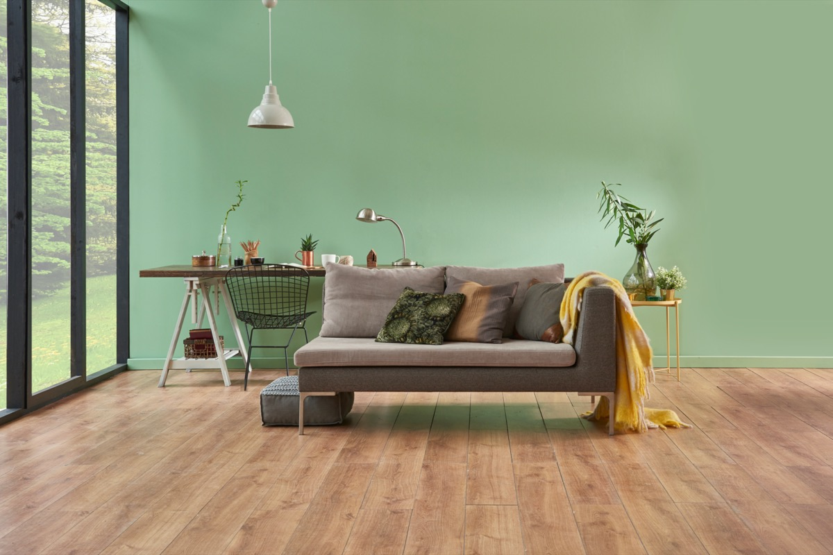 green room with gray couch and large windows