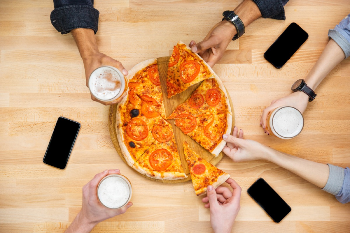 hands reaching for slices on pizza across table with phones and pints of beer on it