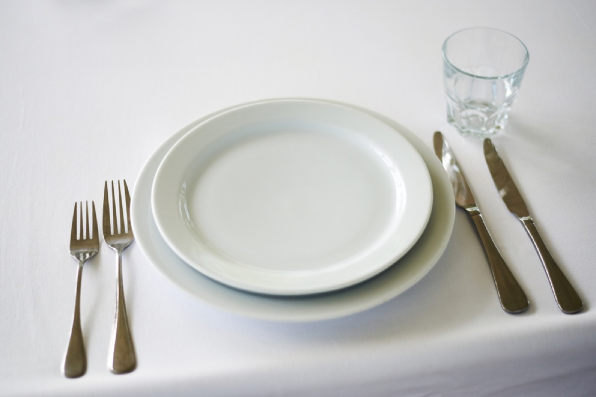 white plates and two sets of forks and knives on white tablecloth