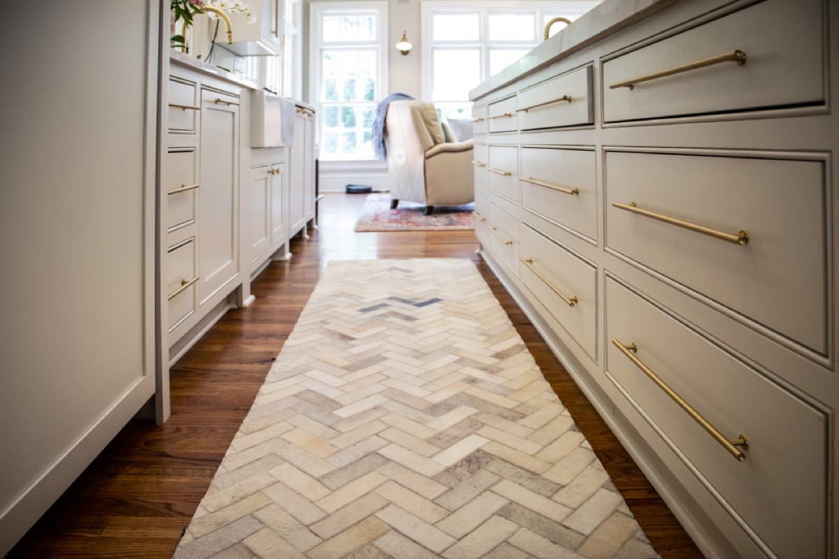white brick patterned runner rug between two rows of lower kitchen cabinets