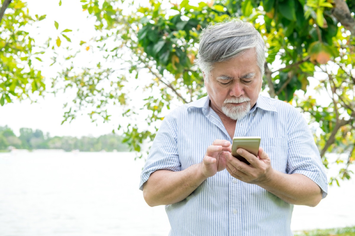 senior asian man confused by cell phone