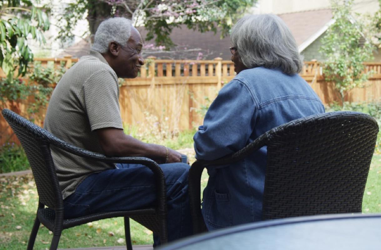 senior black couple talks outside in backyard