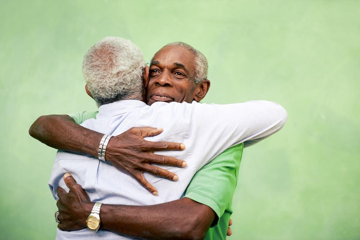 Two senior black men hugging outdoors