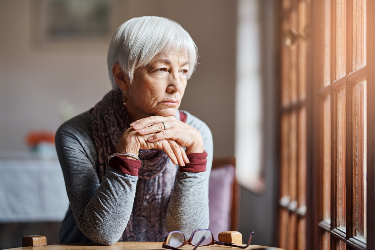 senior woman looking thoughtful as she stares out window