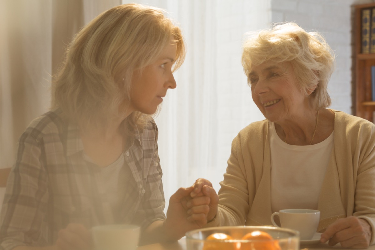 Senior woman smiling at daughter who looks concerned