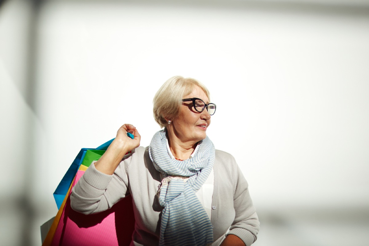 senior woman holding shopping bags while standing against white wall