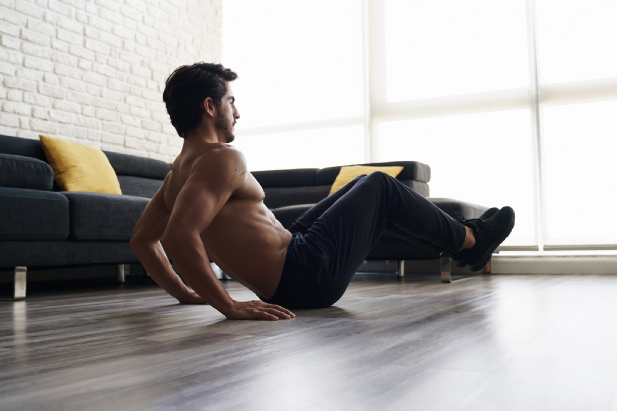 shirtless white man doing a knee tuck exercise at home