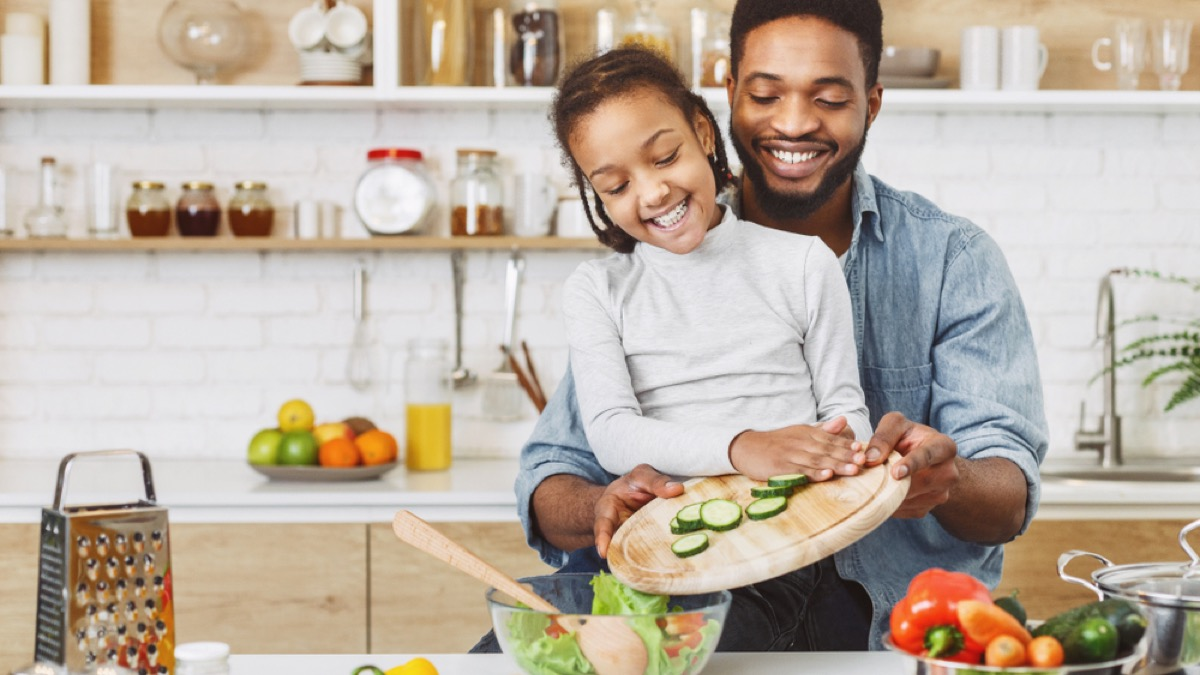 black father helping daughter push cucumbers into a salad bowl