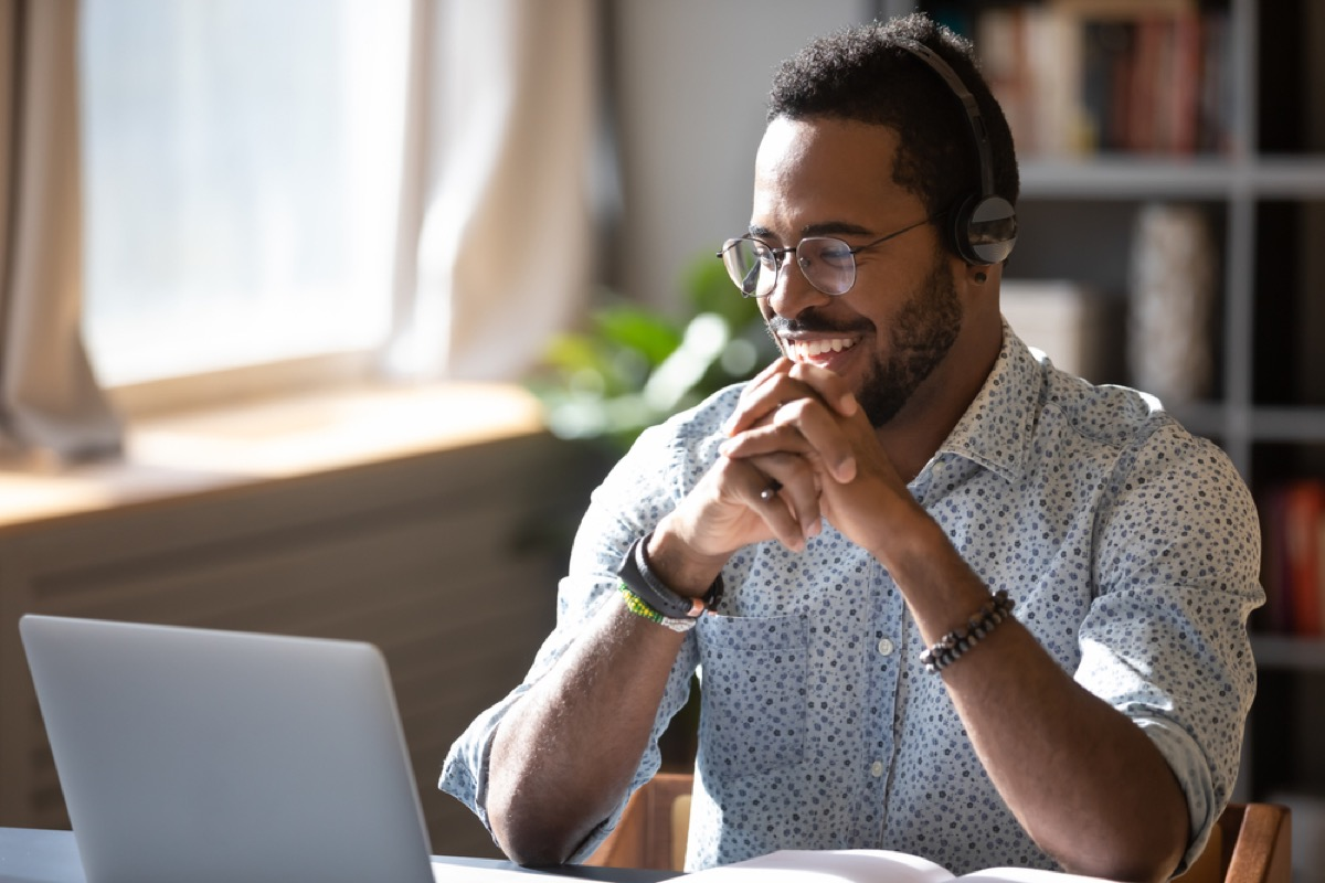 young black man smiling and chatting on his laptop