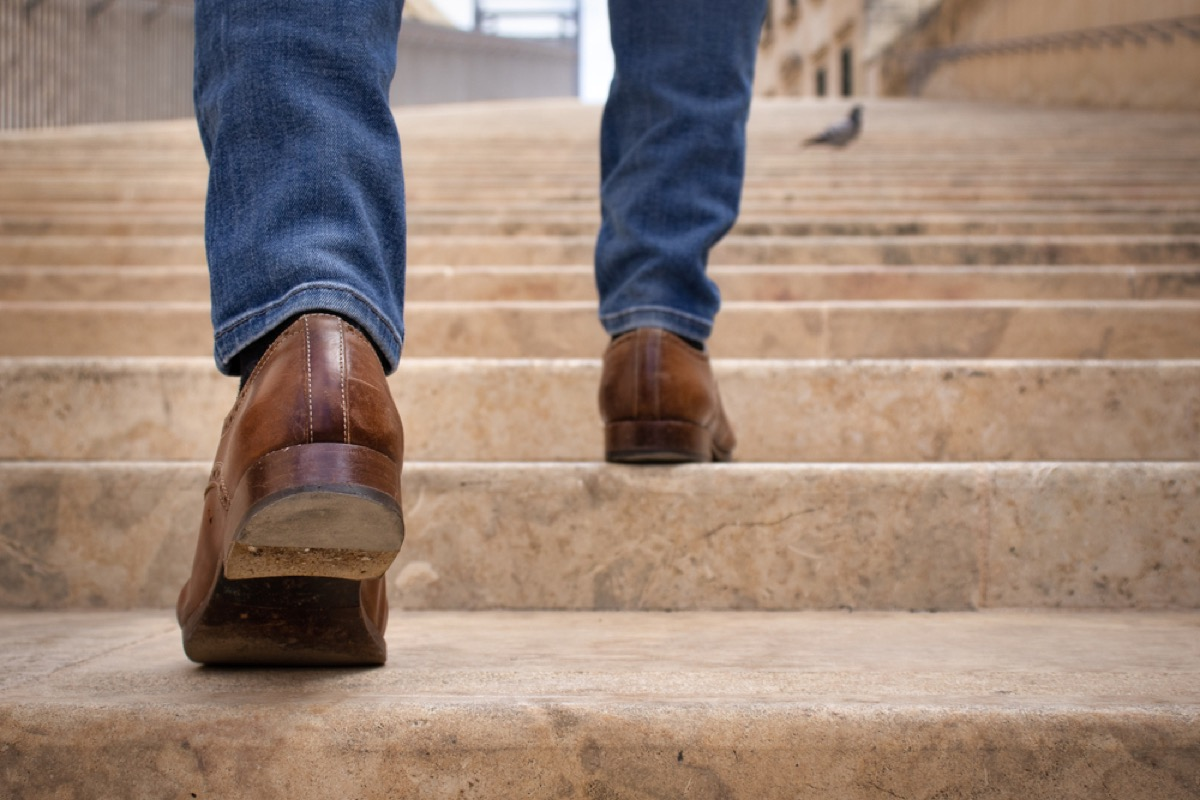 close up of man's legs walking up stairs