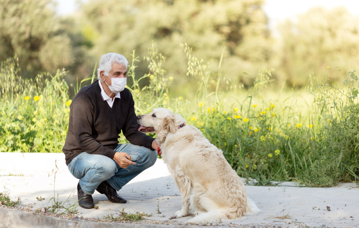older white man with a face mask crouching down next to his dog outside