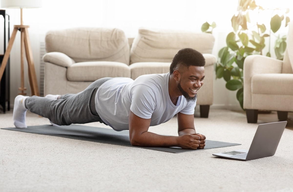 young black man doing a plank in front of his laptop at home