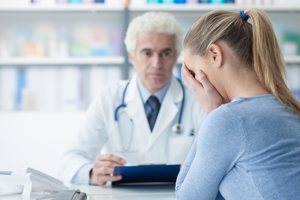 female patient receives bad news with older male doctor