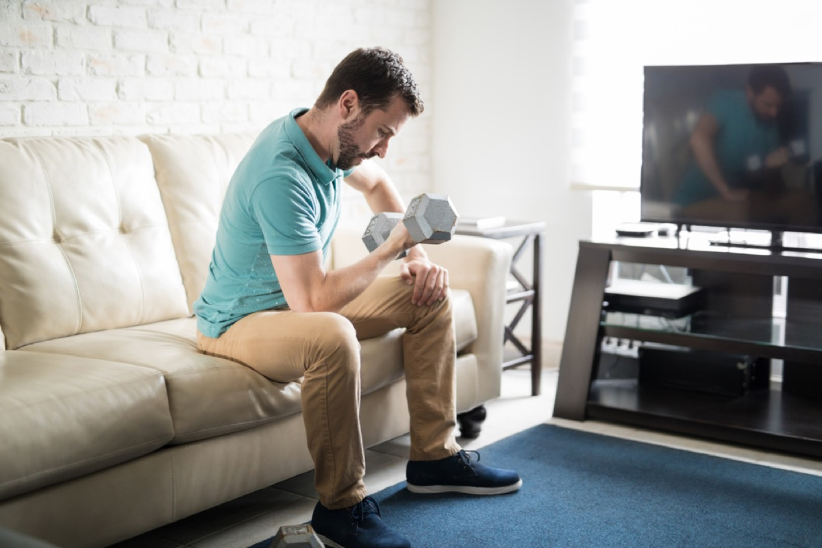 white man lifting weights while sitting on his couch in front of tv