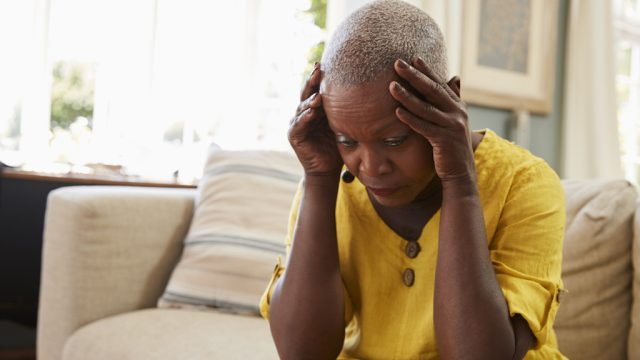 woman, holding head while sitting on couch, has dementia