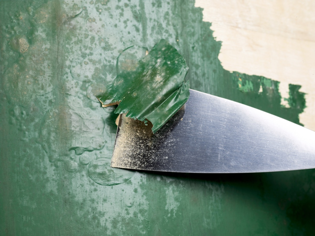 stripping green paint with metal scraper