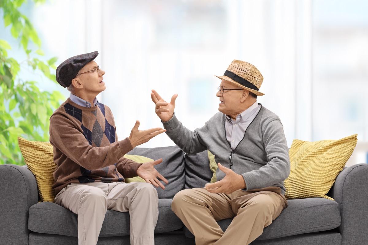 Senior men sitting on couch arguing
