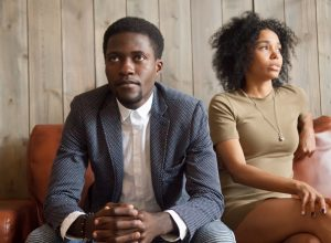 upset-looking 30-something black couple sitting on couch