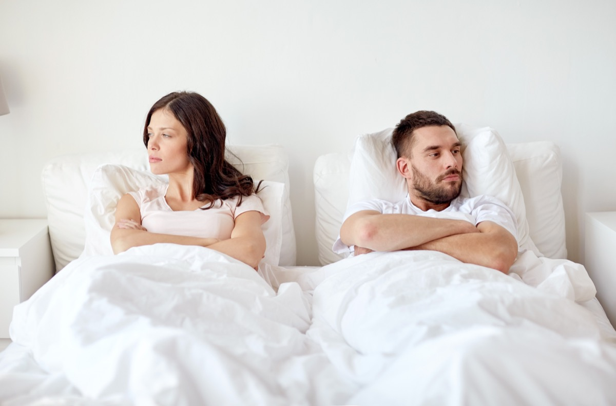 upset white couple in bed