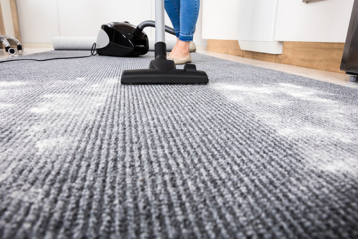 woman vacuuming up powder from carpet, easy home tips