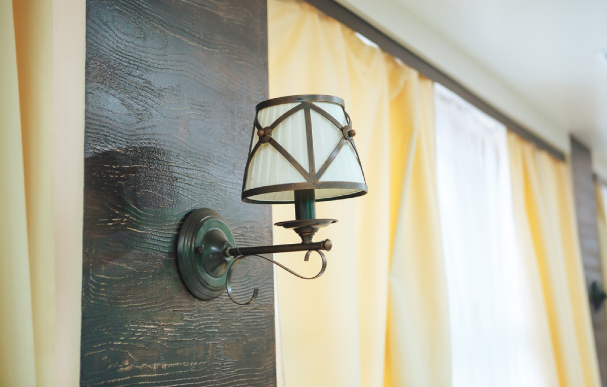 vintage inspired wall sconce next to window with yellow curtain